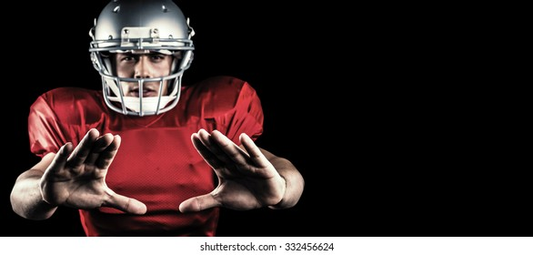 Portrait of sportsman defending while playing American football against black