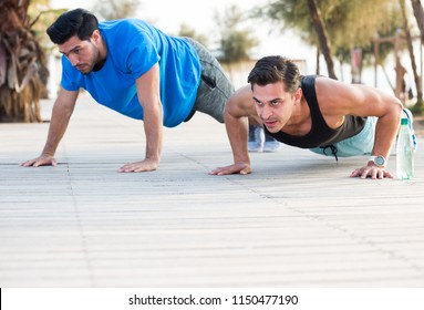 Portrait of sportsmen who are pushing-up in the park near sea.