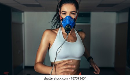 Portrait of sportswoman with mask running on treadmill in gym. Female athlete in sports science lab measuring her performance.