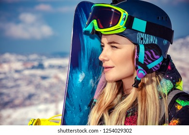 Portrait of a sportswoman wearing helmet and mask with snowboard in hand looking a side, enjoying sunny frosty day, perfect day for snowboarding