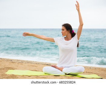 Portrait of sportswoman which is sitting and practicing asana in white T-shirt on the beach.