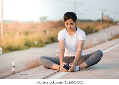 Portrait of sporty Asia woman sitting stretching exercises in roadside. Female athlete preparing for jogging outdoors.