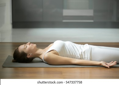 Portrait of sporty attractive woman practicing yoga, lying in Corpse, Dead Body exercise, Savasana pose, resting after working out, wearing white sportswear, indoor, home interior background