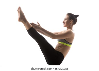 Portrait of sporty beautiful young brunette woman in sportswear working out, doing Teaser Exercise, Boat Pose, Paripurna Navasana, studio full length, isolated shot on white background