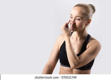 Portrait of sporty beautiful young woman practicing yoga, nadi shodhana pranayama (Alternate Nostril Breathing), copy space, studio