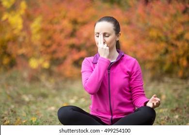 Portrait of sporty beautiful young woman practicing yoga nadi shodhana pranayama (Alternate Nostril Breathing) while sitting in Easy Pose, Sukhasana wearing bright sweatshirt on autumn day