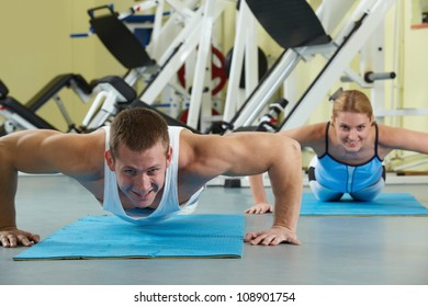 Portrait of sporty couple doing physical exercise and smiling at camera