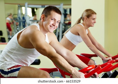 Portrait of sporty couple doing physical exercise on special equipment