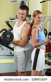 Portrait of sporty couple with dumbbells smiling at camera in gym