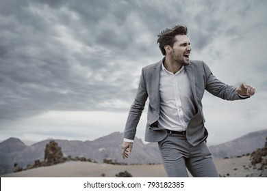 Portrait of a sporty elegant man standing against stong wind on desert.