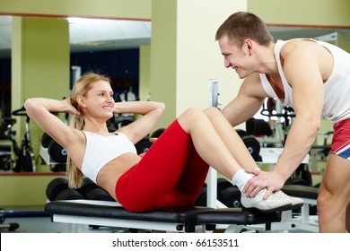 Portrait of sporty female doing physical exercise and interacting with her trainer