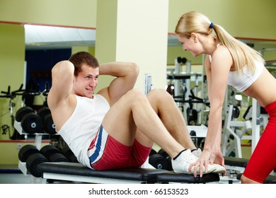 Portrait of sporty female helping handsome guy do physical exercise in gym