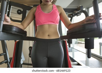 Portrait of sporty female with sport  equipment while standing in gym, weight loss concept