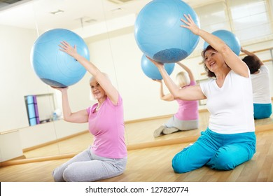 Portrait of sporty females doing physical exercise with fitness balls in sport gym