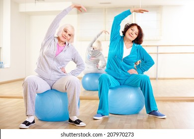Portrait of sporty females doing physical exercise on balls in sport gym