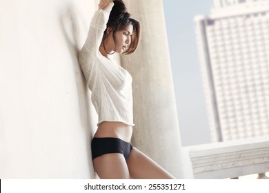 Portrait sporty girl with tiny and sporty belly near with wall