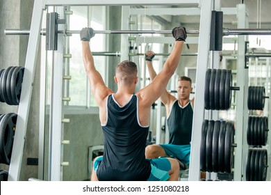 portrait of sporty girl workout on exercise machine in gym. Pretty young man training in the gym