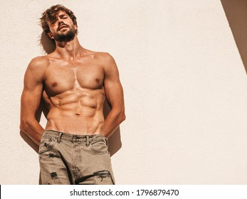 Portrait of sporty handsome strong man. Healthy athletic fitness model posing near white wall in jeans. Confident sexy fashion male with naked nude torso. Lambersexual outdoors