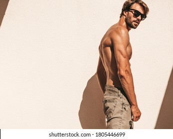 Portrait of sporty handsome strong man. Healthy athletic fitness model posing near white wall in jeans. Confident sexy fashion male with naked nude torso. Lambersexual outdoors in sunglasses