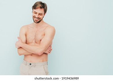Portrait of sporty handsome strong man. Healthy smiling athletic fitness model posing near light blue wall. Confident sexy fashion male with naked nude torso. Lambersexual in studio