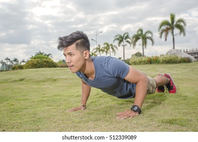 Portrait of sporty happy men doing stretching exercises in park before training. Male athlete preparing for jogging outdoors. Runner doing lunge exercises. Sport active lifestyle concept