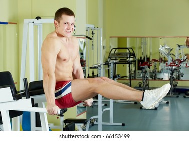 Portrait of sporty man doing exercise in gym and looking at camera