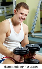 Portrait of sporty man with dumbbells looking at camera
