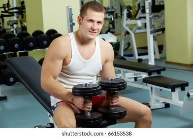 Portrait of sporty man with dumbbells looking at camera in gym
