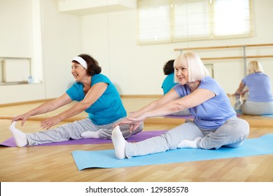 Portrait of sporty mature females doing stretching exercise in sport club