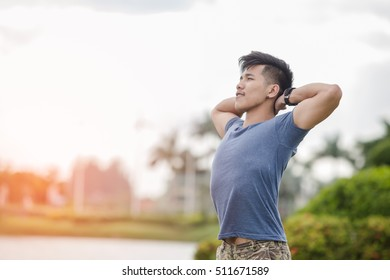 Portrait of sporty men doing stretching exercises in park before training. Male athlete preparing for jogging outdoors. Sport active lifestyle concept. In the evening sunshine.