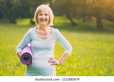 Portrait of sporty senior woman holding exercise mat. Image is intentionally toned.