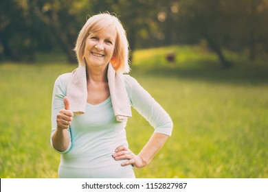 Portrait of sporty senior woman showing thumb up and standing in the nature.Image is intentionally toned.