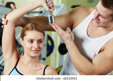 Portrait of sporty woman doing exercise with dumbbell and her trainer supporting