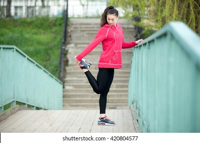 Portrait of sporty woman doing stretching workout in park before jogging. Female athlete runner getting ready for running routine on the bridge. Sport active lifestyle concept. Full length
