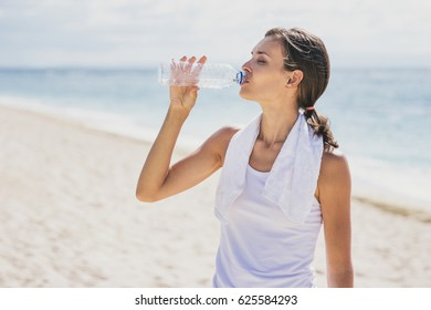 portrait of sporty woman drinking mineral water after workout at the beach