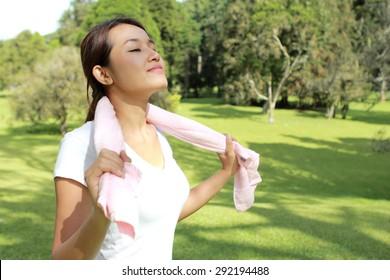 新鮮な空気を持つ公園で日差しの下でリラックスして幸せな気持ちのスポーティーな女性のポートレート
