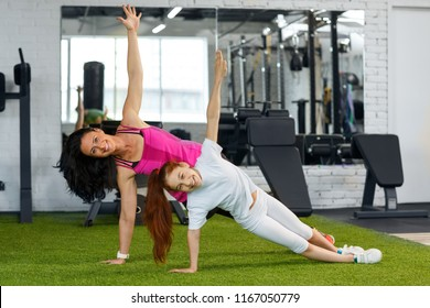 Portrait of sporty woman and little cute girl doing side plank, yoga pose on floor, leaning on one hand and second lifting up. Happy mother and active daughter smiling and looking at camera at gym.