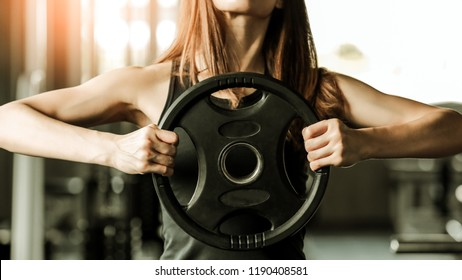 Portrait of sporty woman working out in professional gym holding big dumbbell in hand. Strong, sexy girl excersie in sport club, sport healthcare concept. Vintage tone.
