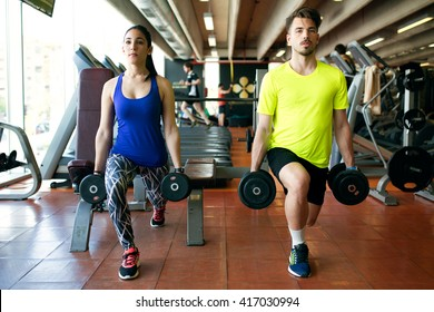 Portrait of sporty young couple doing muscular exercise in gym.