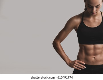 Portrait of sporty young woman with muscular body, posing against a gray background