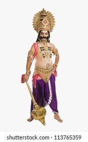 Portrait of a stage artist dressed-up as Ravana and holding a mace