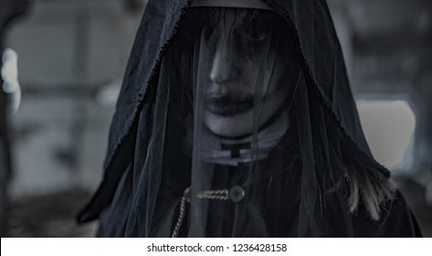 Portrait of standing in a darkness woman dressed in a black hooded cloak in an image of a nun possessed by demons. Cosplay.