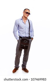 Portrait of standing handsome man posing in studio with bag and glasses