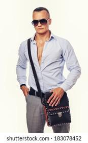 Portrait of standing handsome man posing in studio with bag