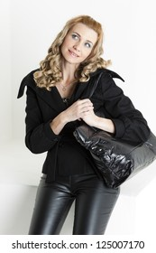 portrait of standing woman in black clothes with a handbag