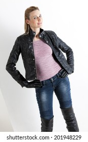 portrait of standing woman wearing jeans and black boots