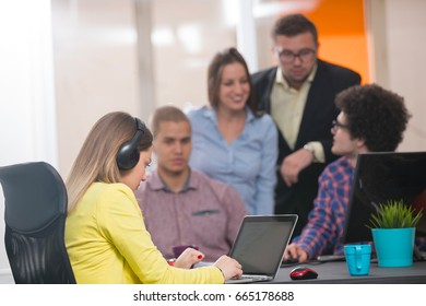 Portrait of startup group of creative people having a meeting with a laptop in a modern office. Business people having relaxed conversation over new project in coworking space