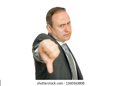 A portrait of a stern, angry business man giving a thumbs down signal on a white background with copy space.