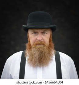 Portrait of a stern bearded man in braces and bowler hat staring intently at the camera