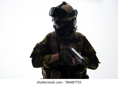 Portrait of stern soldier wearing uniform while holding modern pistol in hands. Military concept. Isolated